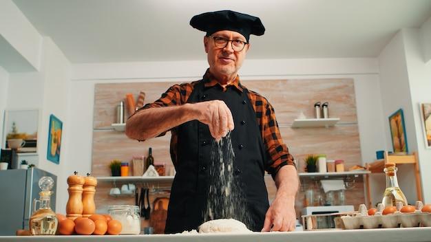 Senior man meel op deeg toevoegen met de hand kijken camera glimlachen. gepensioneerde bejaarde chef-kok met bonete en uniform besprenkelen, zeven, verspreiden van nieuwe ingrediënten met handbakken zelfgemaakte pizza en brood
