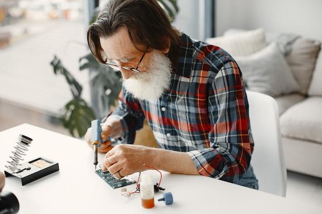 Senior man met apparatuur om te solderen. thuiswerken.
