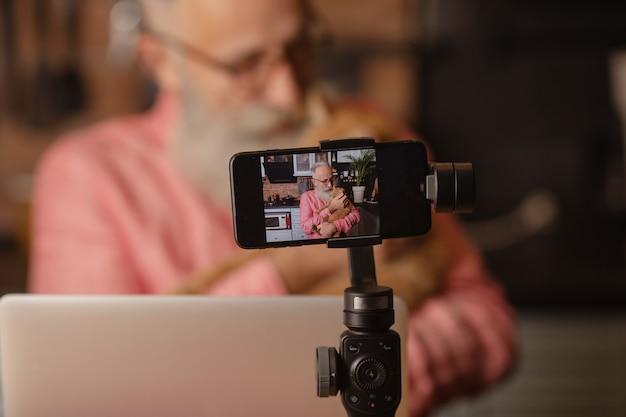 Senior man met baard maakt een blog, een volwassen man speelt met een kat.