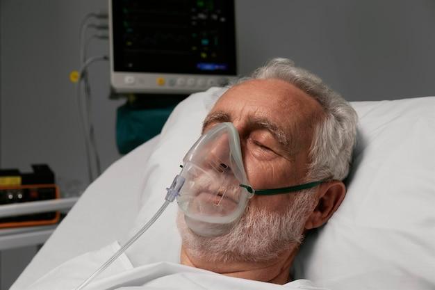 Senior man met beademingsapparaat in een ziekenhuisbed