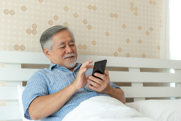 Senior man met behulp van een smartphone, glimlachend thuis gelukkig voelen in bed.