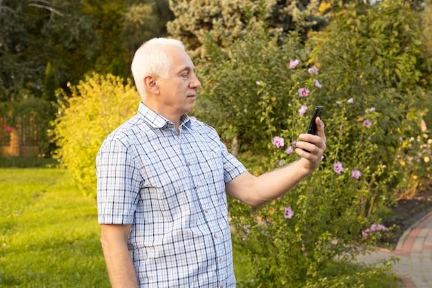 Senior man met behulp van mobiele telefoon in groen park, moderne technologieën