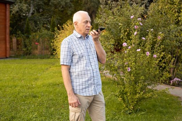 Senior man met behulp van mobiele telefoon met gesproken zoekopdrachten in groen park, moderne technologieën