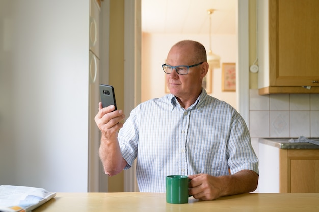 Senior man met behulp van telefoon terwijl het drinken van koffie bij het raam