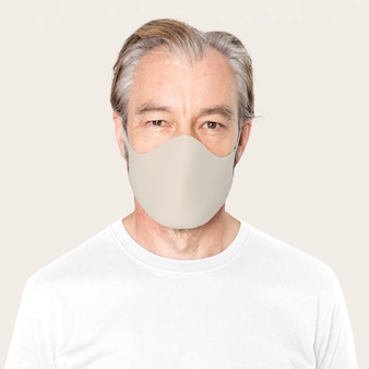 Senior man met beige gezichtsmasker covid-19 campagne met ontwerpruimte