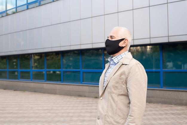 Senior man met beschermend masker in stad in de buurt van kantoorgebouwen uitbraak van virale ziekte coronavirus covid-2019