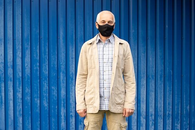 Senior man met beschermend masker op blauwe achtergrond, copyspace, plaats voor tekst, uitbraak van virale ziekte coronavirus covid-2019