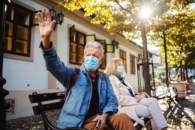 Senior man met beschermend masker op buiten op de bank zitten en zwaaien naar een vriend.