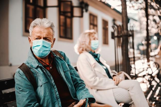 Senior man met beschermend masker op buiten op de bank zitten.