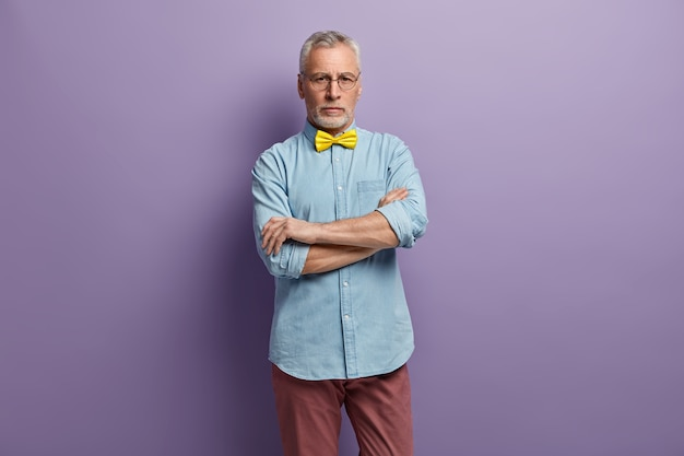 Senior man met blauw shirt en gele bowtie