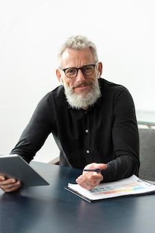 Senior man met bril thuis studeren tijdens het gebruik van tablet
