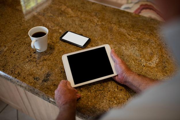 Senior man met digitale tablet in de keuken thuis