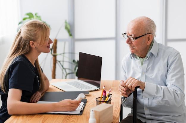 Senior man met een check-up met verpleegster