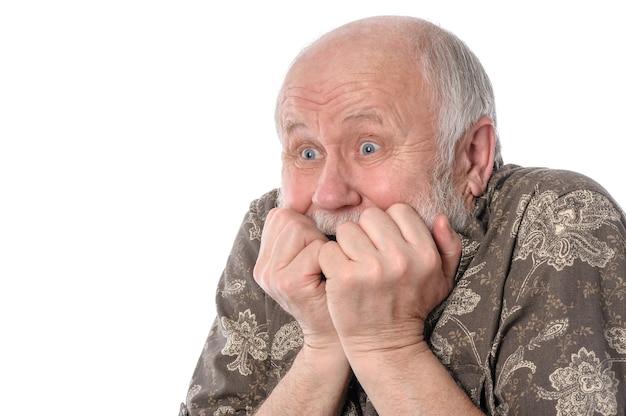 Senior man met een grimas van angst op wit wordt geïsoleerd