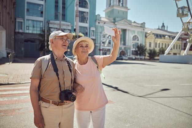 Senior man met een pet en bril en een dame met een zonnehoed die selfies neemt