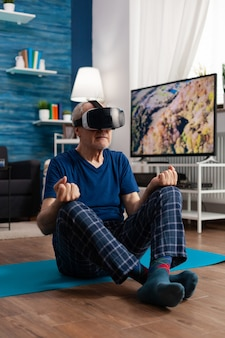 Senior man met een virtual reality-headset die meditatieoefening beoefent, zittend op een yogamat in de woonkamer, de lichaamsspier uitrekkend