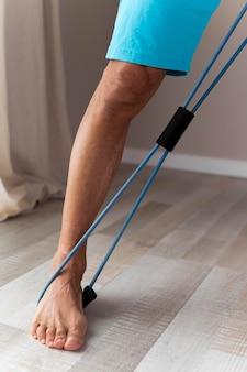 Senior man met fitness accessoires binnenshuis