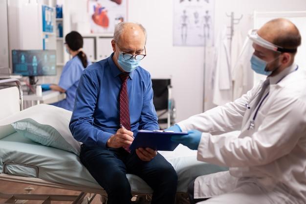 Senior man met gezichtsmasker die een overeenkomst ondertekent in het onderzoeksbureau van het ziekenhuis in de tijd van covid19