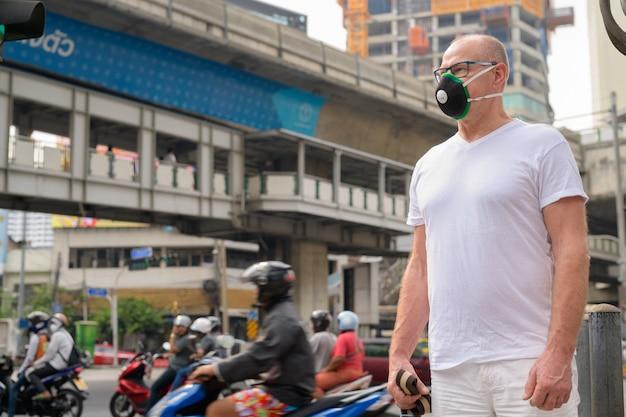 Senior man met gezichtsmasker om te beschermen tegen vervuiling smog in de stad