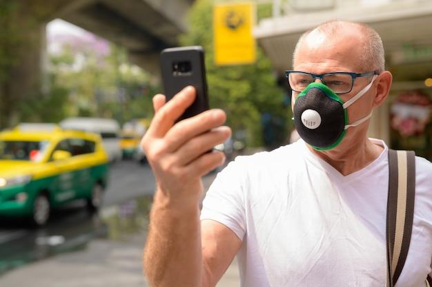 Senior man met gezichtsmasker om te beschermen tegen vervuiling smog