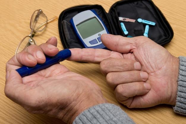 Senior man met glucometer bloedsuikerspiegel thuis controleren