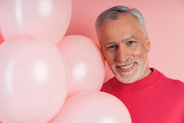 Senior man met grijs haar en baard en roze ballonnen