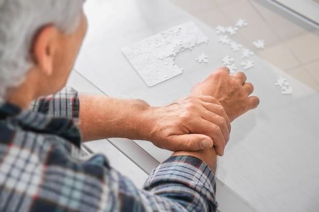 Senior man met het syndroom van parkinson die thuis puzzelt