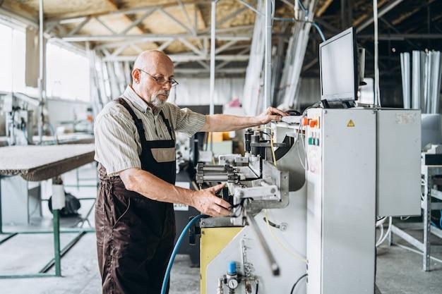 Senior man met kale hoofd, werken in de fabriek voor speciale machine