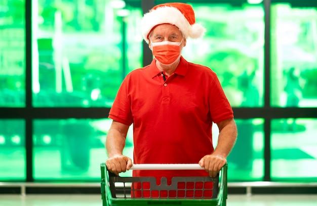 Senior man met kerstmuts met een beschermend gezichtsmasker die de trolley in de supermarkt duwt