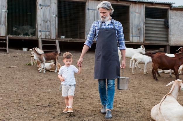 Senior man met kleinzoon op het platteland