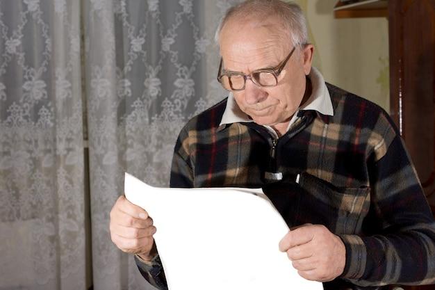 Senior man met leesbril kijken naar een krant