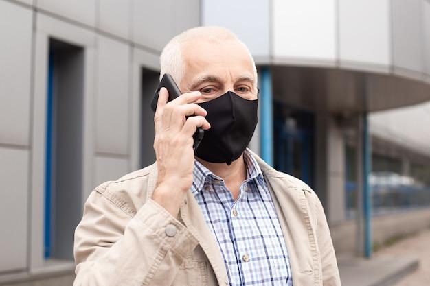 Senior man met masker met smartphone in stad in de buurt van kantoorgebouwen