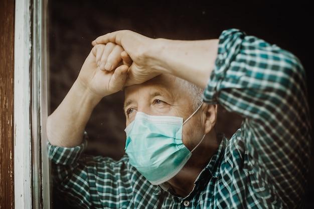 Senior man met medisch masker thuis tijdens coronavirus, covid-2019 pandemie, blijf thuis