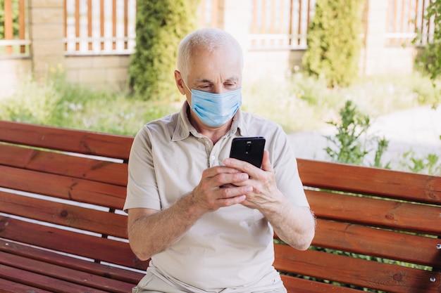 Senior man met medische gezichtsmasker met behulp van de telefoon naar nieuws te zoeken. luchtvervuiling. concept van coronavirus quarantaine.