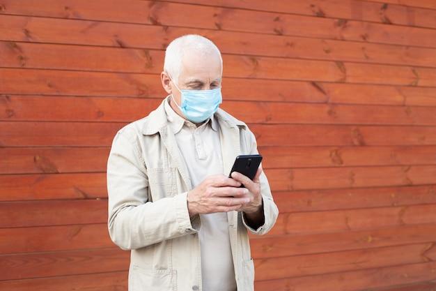 Senior man met medische gezichtsmasker met behulp van de telefoon naar nieuws te zoeken