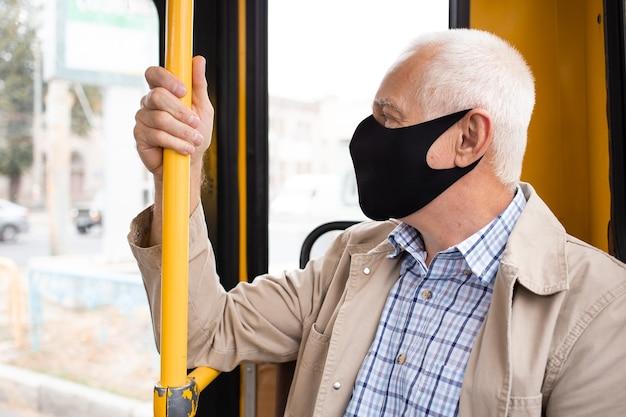 Senior man met medische gezichtsmasker zittend in het busvervoer.