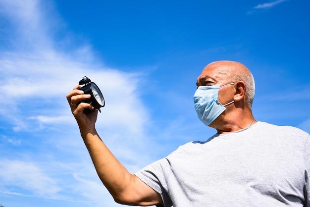 Senior man met medische masker en bril kijken naar de wekker op een blauwe hemel met wolken. coronavirus concept. ademhalingsbescherming. bedrijfsconcept