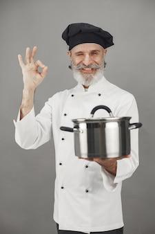 Senior man met metalen pan. chef-kok in een zwarte hoed. professionele benadering van zaken.