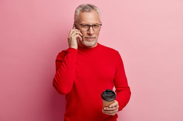Senior man met rode trui en trendy bril