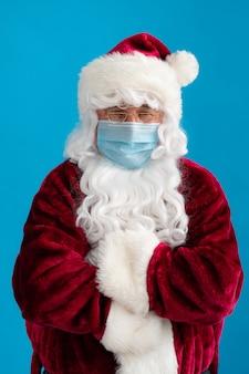 Senior man met santa claus-kostuum en beschermend masker. kerstvakantie tijdens pandemisch coronavirus covid 19-concept