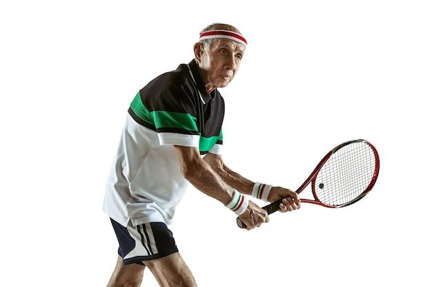 Senior man met sportkleding tennissen geïsoleerd op een witte muur. kaukasisch mannelijk model in topvorm blijft actief en sportief. concept van sport, activiteit, beweging, welzijn. copyspace, advertentie.