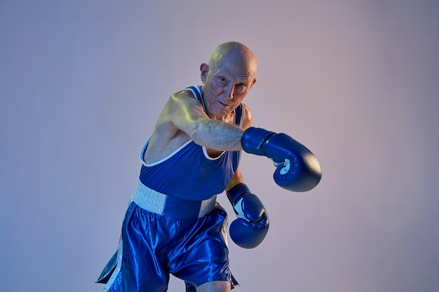 Senior man met sportwear boksen geïsoleerd op de muur van de gradiëntstudio