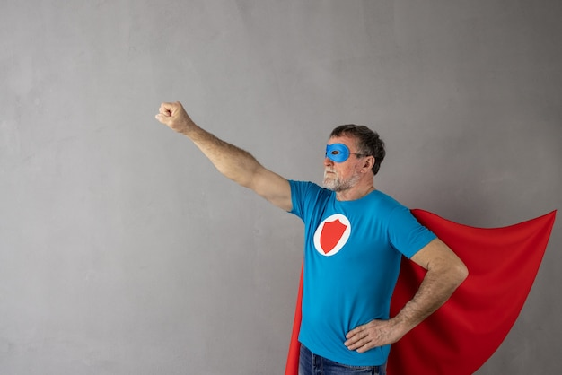 Senior man met superheld kostuum tegen grijze betonnen muur oppervlak