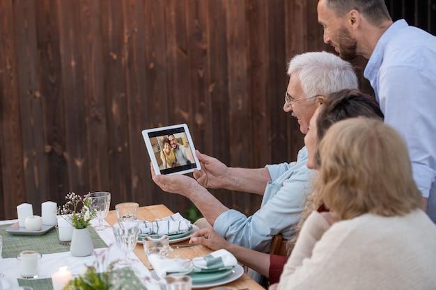 Senior man met tablet terwijl zijn familie communiceert met vrienden in videochat