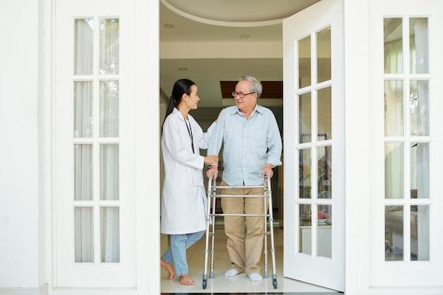 Senior man met verpleegster gaat lopen