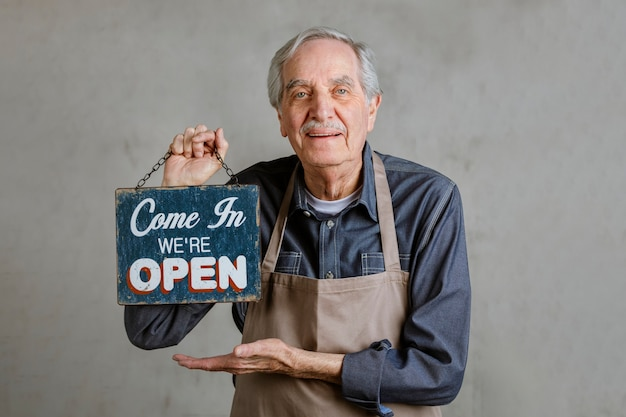 Senior man met winkelbordje, kom binnen, we zijn open