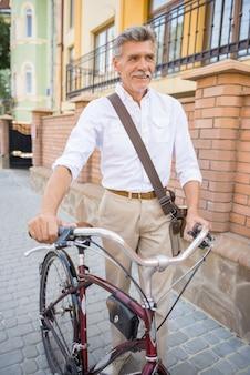 Senior man met zijn fiets in de openbare straten in de stad.