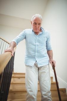 Senior man naar beneden klimmen met wandelstok