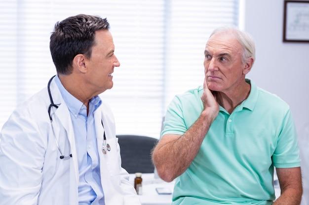 Senior man nekpijn tonen aan arts