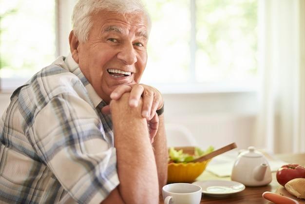 Senior man ontspannen na het ontbijt